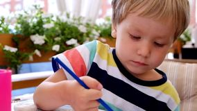 Little boy drawing in a cafe stock footage