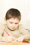 Concentrated boy drawing with crayon Stock Photos