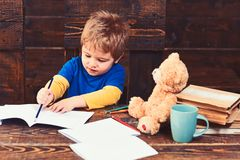 Concentrated boy drawing line with blue pencil. Busy kid writing in exercise book. Pupil on wooden panels background.  stock image