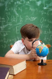Concentrated boy examines globe Royalty Free Stock Image