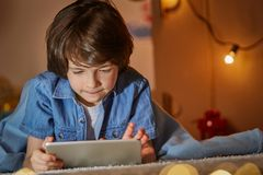 Interested kid surfing internet on tablet stock photos
