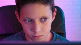 Concentrated boy playing computer game in his fancy room stock footage