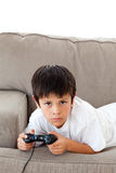 Concentrated boy playing video games. Lying on the sofa at home Stock Photography