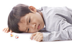 Concentrated boy plays dices on table Royalty Free Stock Photo