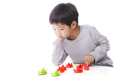 Concentrated boy plays paper ships on table Royalty Free Stock Images