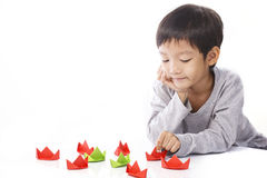 Concentrated boy plays paper ships on table Stock Photo
