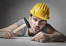 Concentrated brick layer. Brick layer using a hammer Royalty Free Stock Images
