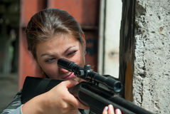 Concentrated  brunette looking in rifle sight Royalty Free Stock Images