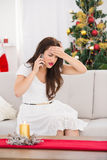 Concentrated brunette on the phone on christmas day Royalty Free Stock Images