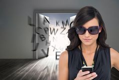 Concentrated brunette wearing sunglasses texting Royalty Free Stock Photography