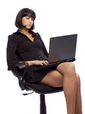 Concentrated brunette woman in dark dress sitting. In the office chair and working on laptop over white background Royalty Free Stock Photo