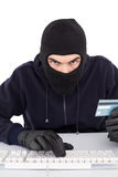Concentrated burglar in balaclava shopping online Royalty Free Stock Photo