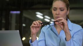 Concentrated business lady taking eyeglasses working laptop, eyesight problem stock video footage