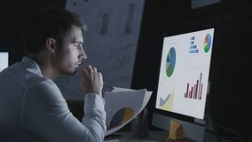 Concentrated business man analyzing financial document in night office. Concentrated business man analyzing financial document front computer in night office stock video footage