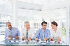 Concentrated business team sitting with their vote on the desk Royalty Free Stock Image