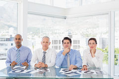 Concentrated business team sitting with their vote on the desk Royalty Free Stock Photo