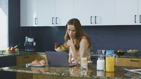 Business woman checking email. Thinking female freelancer working on computer. Concentrated business woman checking email standing on luxury kitchen. Thinking stock footage