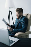 Concentrated businessman in armchair reading newspaper Stock Photos
