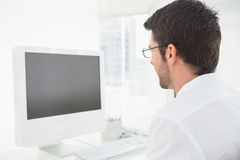 Concentrated businessman with glasses using computer Stock Photo