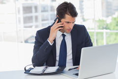 Concentrated businessman having a phone call and working on his Stock Photos