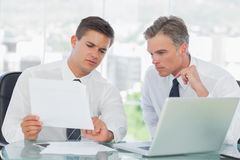 Concentrated businessman listening to his intern while explainin Stock Photo