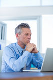 Concentrated businessman looking at laptop computer Stock Image
