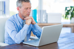 Concentrated businessman looking at laptop computer Royalty Free Stock Images