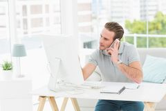 Concentrated businessman on the phone using computer Stock Images