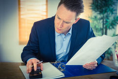 Concentrated businessman reading a document Stock Images