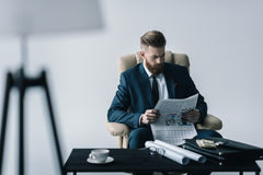 Concentrated businessman reading newspaper in office Royalty Free Stock Photography