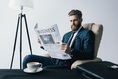 Concentrated businessman reading newspaper in office Stock Photography