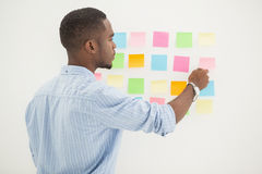 Concentrated businessman reading sticky notes Stock Photography