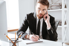 Concentrated businessman talking by phone and writing notes. Photo of concentrated businessman sitting in office while talking by phone and writing notes Stock Image