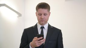 Concentrated businessman texting on his smartphone. Front view successful young executive manager, businessman, concentrains his attention while typing an stock footage