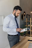 Concentrated businessman using calculator while standing at workplace. Side view concentrated businessman using calculator while standing at workplace Stock Image