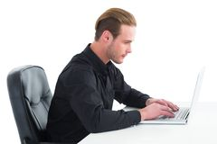 Concentrated businessman using laptop at desk Stock Images
