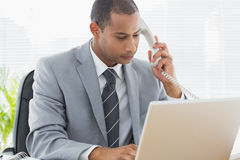 Concentrated businessman using laptop and phone Royalty Free Stock Photos