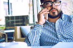 Concentrated businessman using mobile phone. Arabic businessman in glasses and beard having a phone talk seateing in the royalty free stock photo