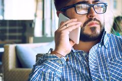 Concentrated businessman using mobile phone. Arabic businessman in glasses and beard having a phone talk seateing in the royalty free stock photos