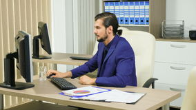 Concentrated businessman working at his computer. Office and corporate work stock footage