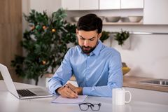 Concentrated businessman working at home stock photo