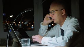 Concentrated businessman working on laptop and talking by phone in dark office. Executive business man calling by smartphone while night work in office stock footage