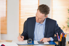 Concentrated businessman writing down Royalty Free Stock Photography