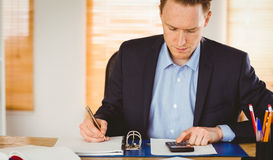 Concentrated businessman writing down Stock Images