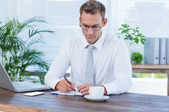 Concentrated businessman writing on a notebook Stock Images