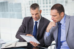Concentrated businessmen analyzing documents on their tablet Stock Photography