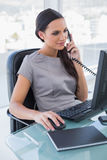 Concentrated businesswoman answering phone and working on comput Royalty Free Stock Image