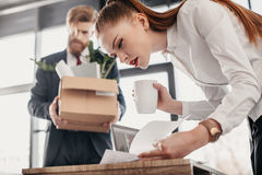 Concentrated businesswoman with documents and upset fired businessman with cardboard box behind Stock Images