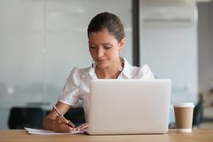Concentrated businesswoman handwriting making notes working in office. Focused businesswoman writing signing document working on laptop in office, concentrated royalty free stock photos