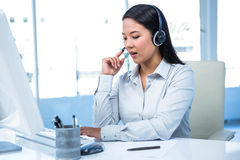 Concentrated businesswoman with headset using computer Royalty Free Stock Images